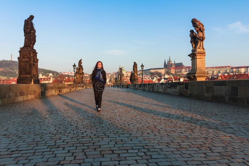 De gelukkige jonge vrouw met lang haar loopt door de Charles-brug praag Tsjechische Republiek royalty-vrije stock foto