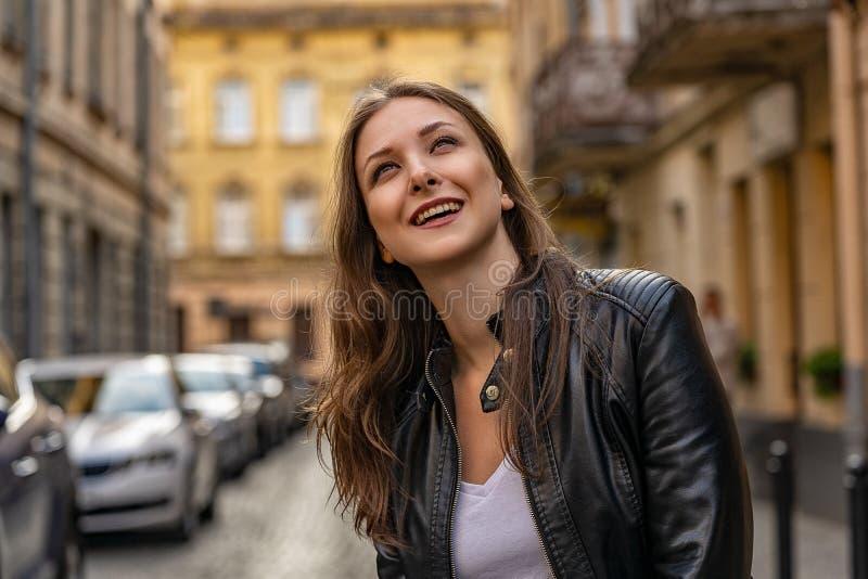 De gelukkige jonge vrouw op de straat van oude stad glimlacht omhoog en kijkt stock foto