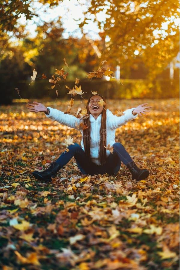 De gelukkige jonge vrouw in park op zonnige de herfstdag, het lachen, het spelen gaat weg Vrolijk mooi meisje in witte sweater ti royalty-vrije stock foto's