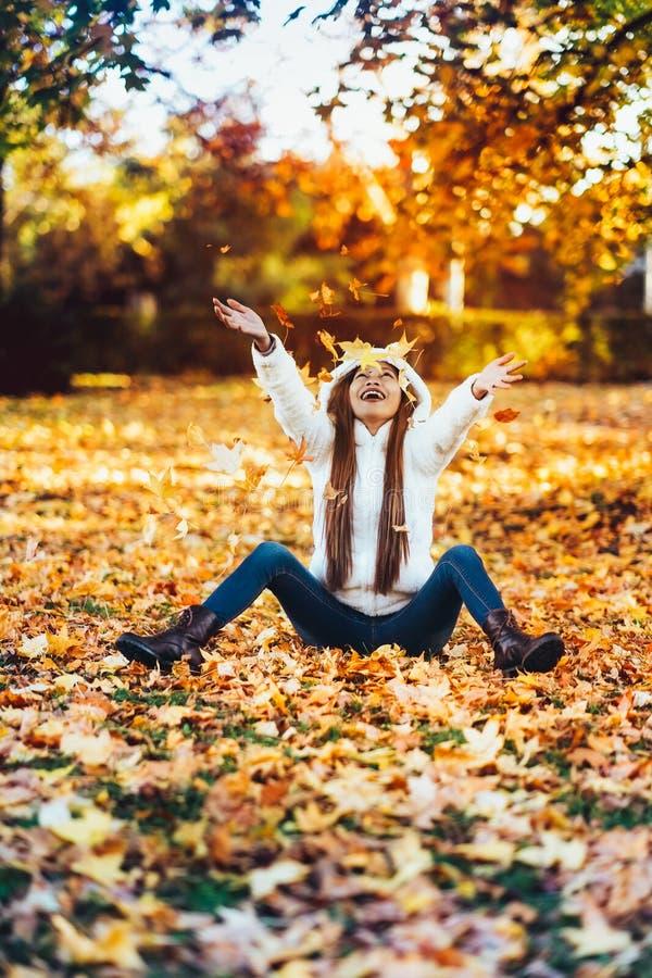 De gelukkige jonge vrouw in park op zonnige de herfstdag, het lachen, het spelen gaat weg Vrolijk mooi meisje in witte sweater ti stock afbeeldingen