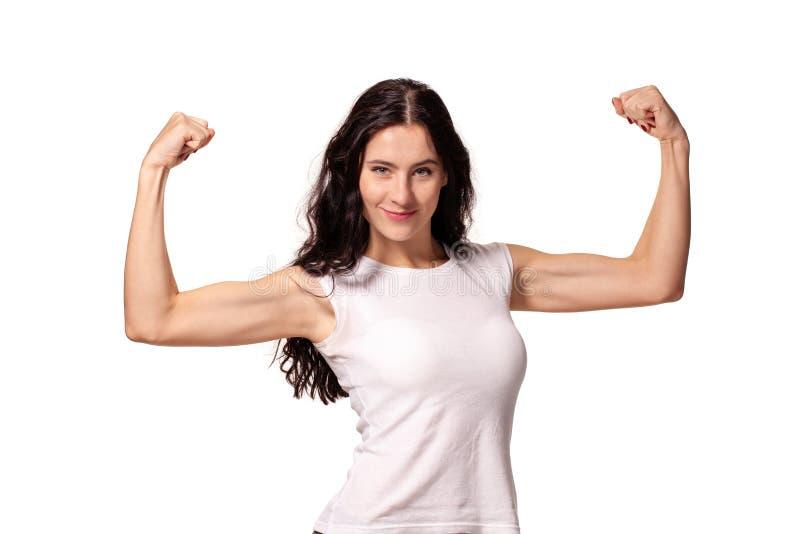 De gelukkige jonge vrouw toont haar spieren die op witte achtergrond worden ge?soleerd stock fotografie