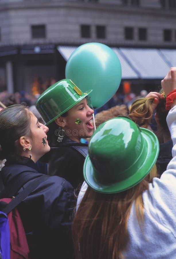 De gelukkige jonge vrouwen met groene bowlingspelerhoeden en de ballons die bij St Patrick's Dag toejuichen paraderen in de str stock fotografie