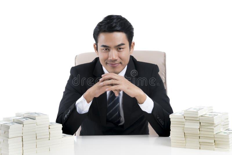 De gelukkige Jonge zakenman clasped handen en grote stapel van geld stock afbeeldingen