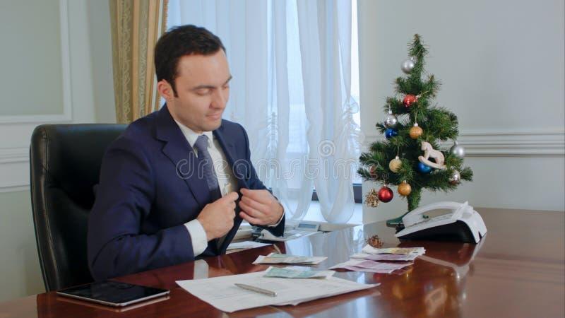 De gelukkige jonge zakenman telt salaris dichtbij Nieuwjaarboom in bureau stock fotografie