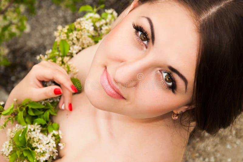De gelukkige jonge zakken van de meisjesholding op een witte achtergrond Mooi jong meisje met bloemen in handen stock foto's