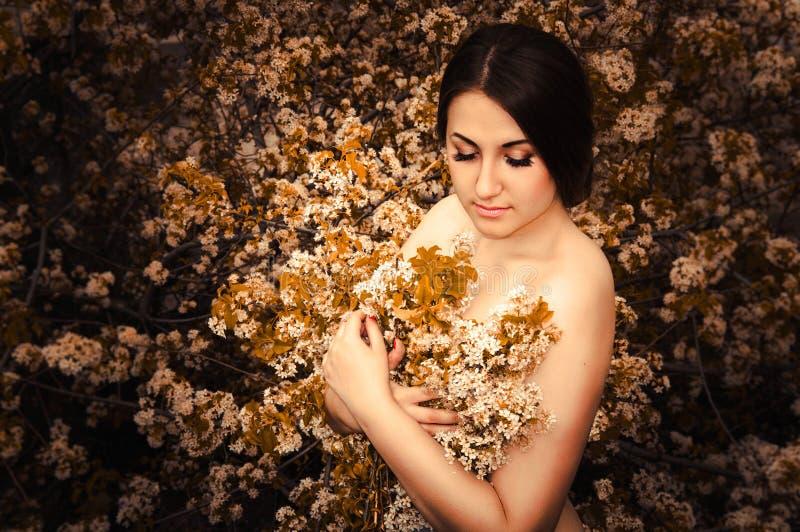 De gelukkige jonge zakken van de meisjesholding op een witte achtergrond Mooi jong meisje met bloemen in handen stock afbeeldingen