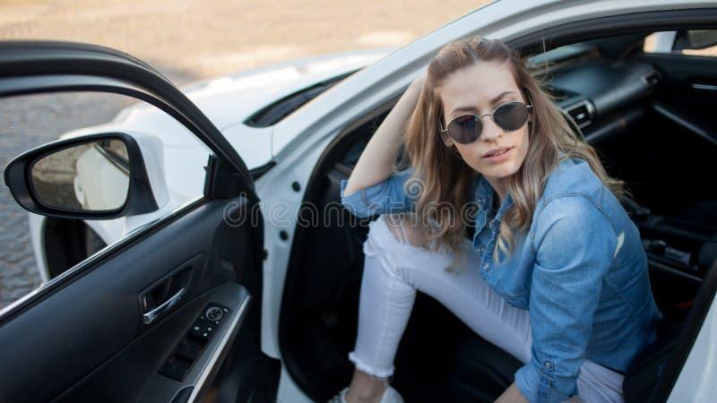 De gelukkige jonge zitting van de blondevrouw in een witte auto Portret van een succesvolle aantrekkelijke vrouw royalty-vrije stock fotografie