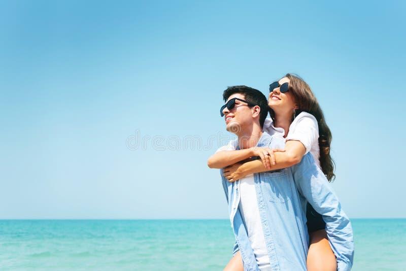 De gelukkige Jonge zonnebril die van de paarslijtage pret op blauwe hemel en het strand hebben stock fotografie