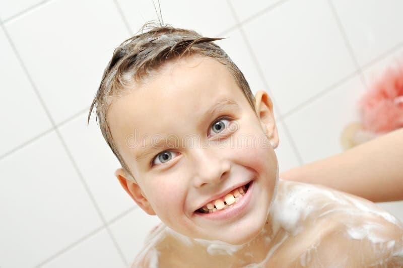 De gelukkige jongen baadt in een badkamers royalty-vrije stock fotografie