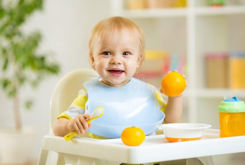 De gelukkige jongen die van het babyjonge geitje gezond voedsel eten stock afbeeldingen