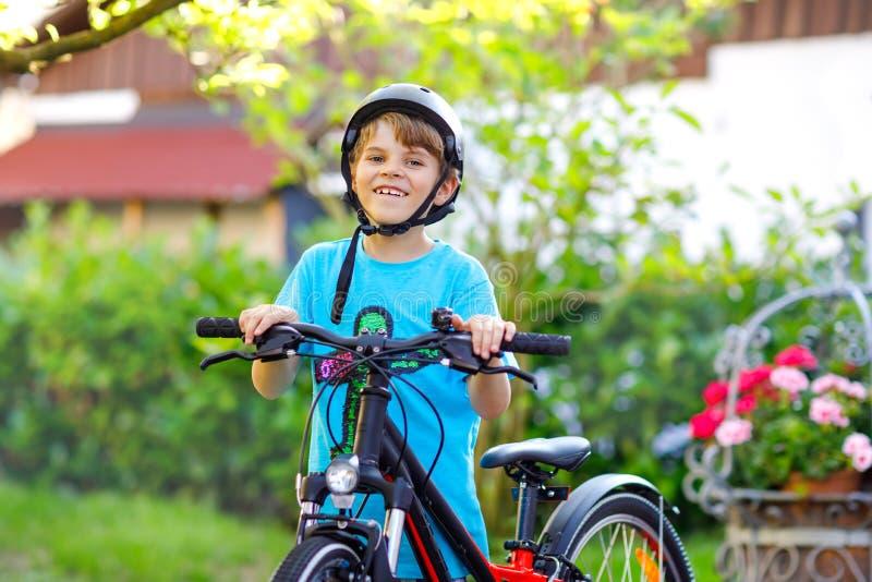 De gelukkige jongen die van het schooljonge geitje pret met het berijden van fiets hebben Actief gezond kind die met veiligheidsh stock afbeelding