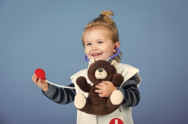 De gelukkige jongen in eenvormige arts onderzoekt stuk speelgoed huisdier met stethoscoop stock foto