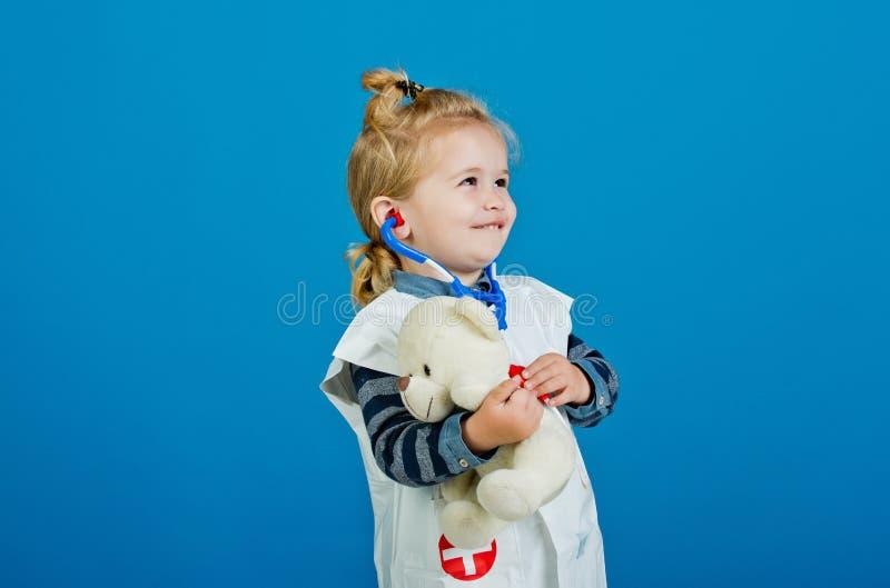 De gelukkige jongen in eenvormige arts onderzoekt stuk speelgoed huisdier met stethoscoop royalty-vrije stock foto
