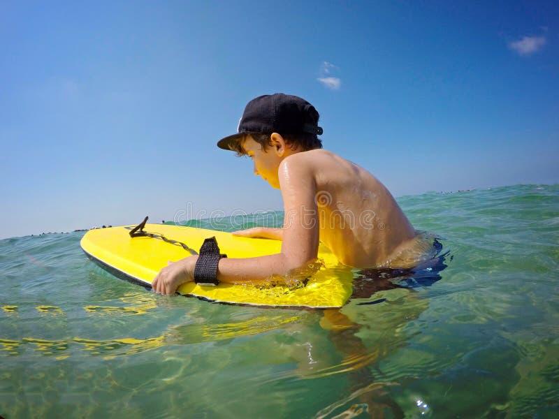 De gelukkige jongen in GLB in zwembroek bevindt zich op het strand op gouden zand en houdt een zwemmende raad, boogie raad van ge royalty-vrije stock foto's