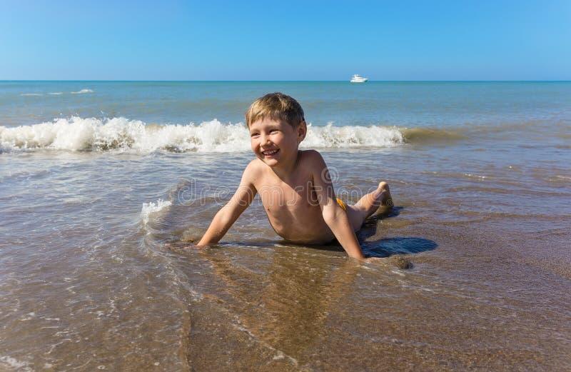 De gelukkige jongen ligt op overzees strand op zonnige dag stock foto's