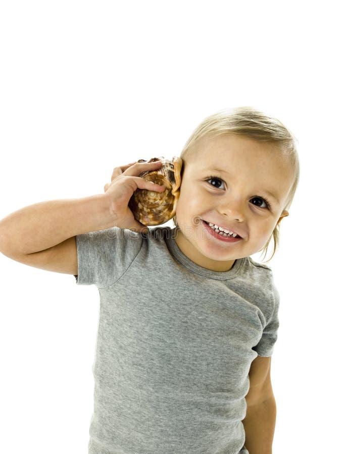 De gelukkige jongen luistert geluid van zeeschelp royalty-vrije stock foto's
