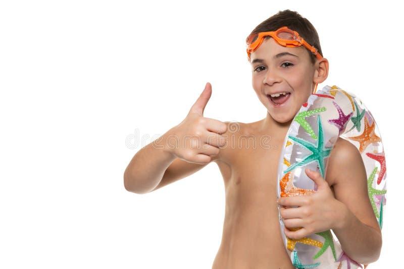 De gelukkige jongen met oranje zwemmende beschermende brillen en een opblaasbare cirkel op zijn schouder, lachen en tonen gebaren royalty-vrije stock foto