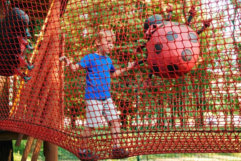 De gelukkige jongen overwint hindernissen in het park van het kabelavontuur De vakantieconcept van de zomer Het leuke jong geitje royalty-vrije stock afbeeldingen
