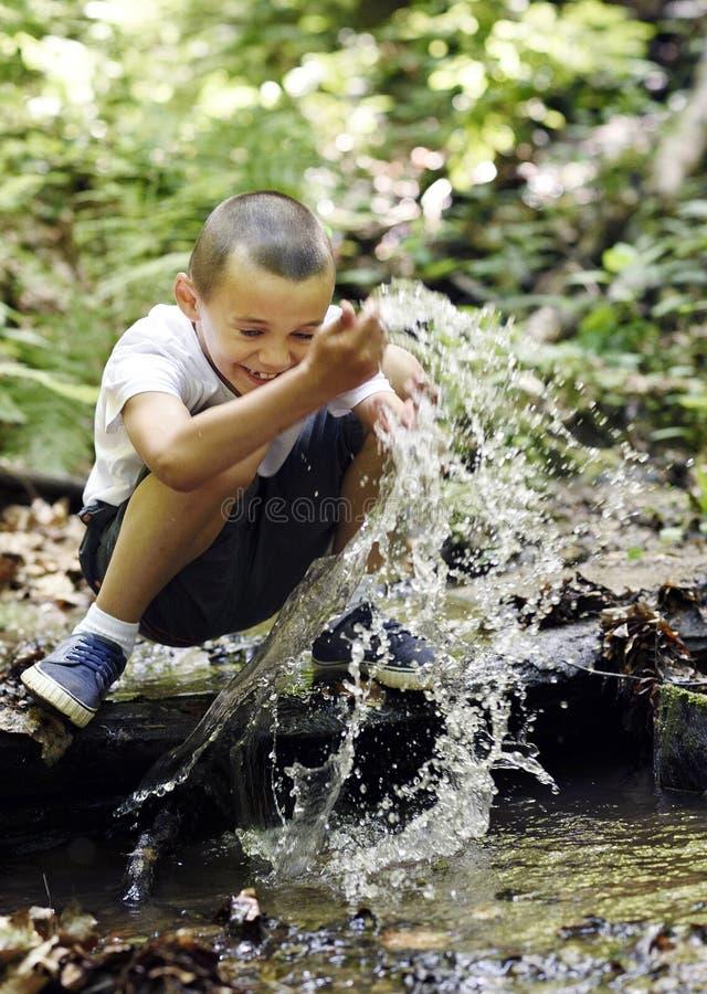 De gelukkige jongen speelt met water stock fotografie