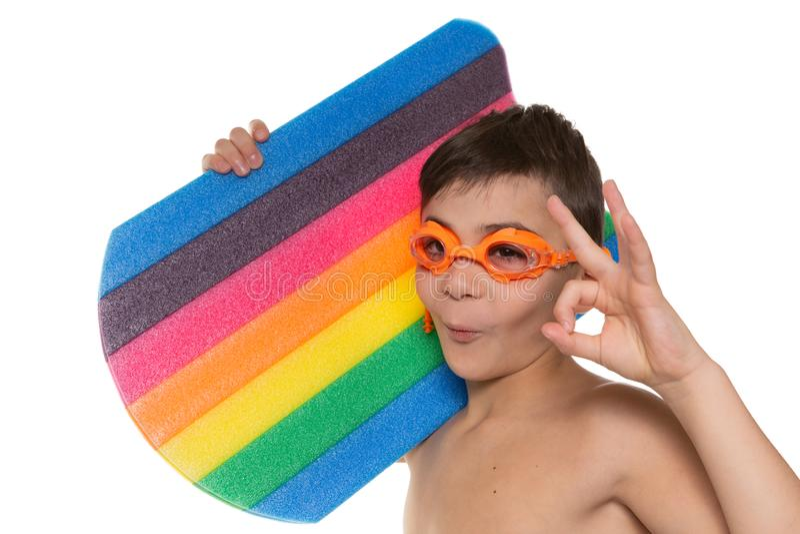De gelukkige jongensatleet met oranje glazen houdt een multicolored zwemmende raad en toont gebaar o.k., concept, op een witte ac stock foto's