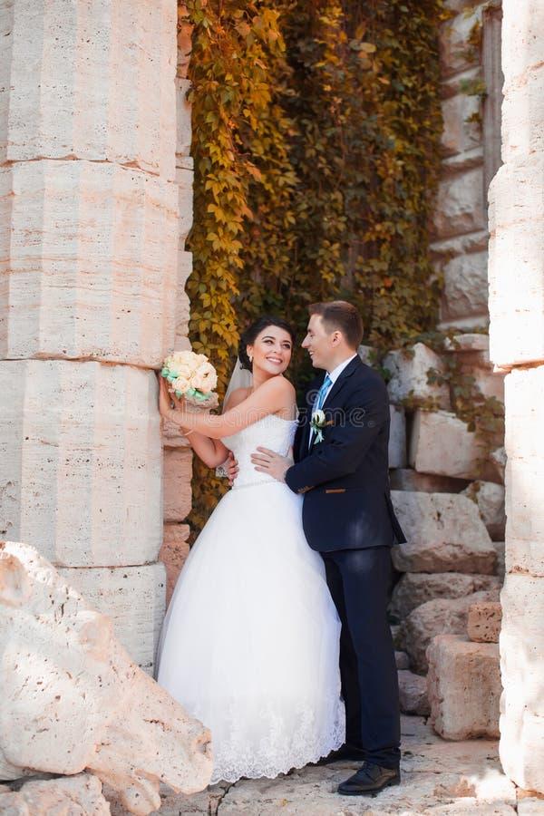 De gelukkige jonggehuwden bevinden zich door de kolom royalty-vrije stock fotografie