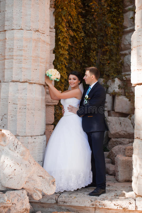 De gelukkige jonggehuwden bevinden zich door de kolom stock fotografie