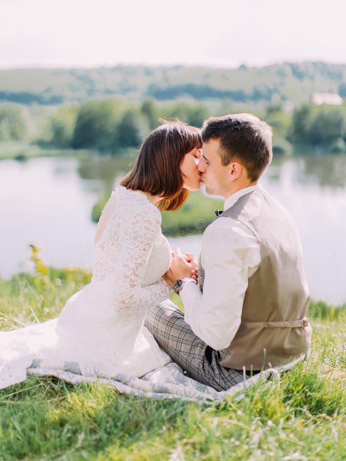 De gelukkige jonggehuwden houden handen en kussen terwijl het zitten op het gras stock fotografie
