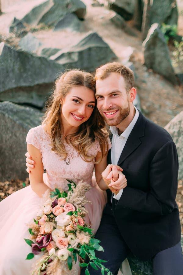 De gelukkige jonggehuwden kijken op een fotograaf De man en de vrouw in feestelijke kleren zitten op de stenen dichtbij de huweli royalty-vrije stock afbeeldingen