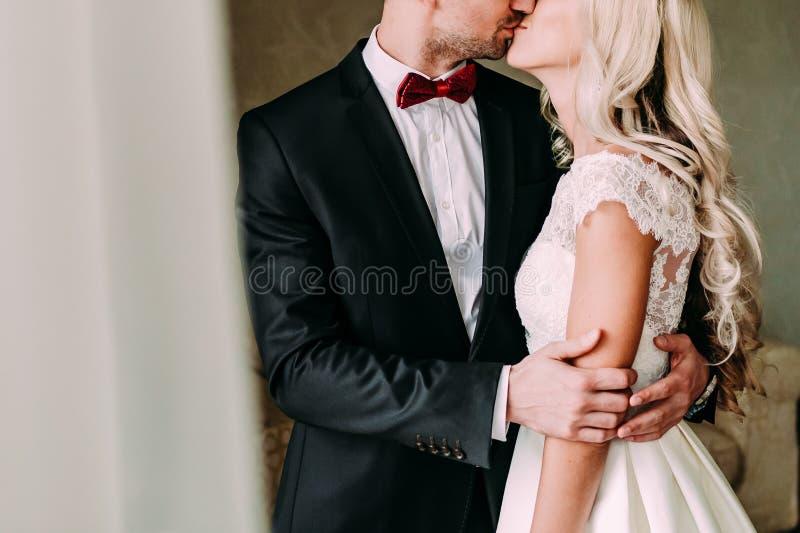 De gelukkige jonggehuwden kussen binnen Een een blodebruid en bruidegom bevinden zich dichtbij het venster Huwelijk royalty-vrije stock foto
