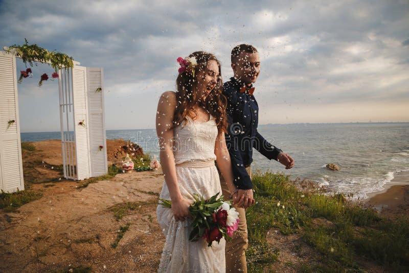De gelukkige jonggehuwden lopen van huwelijksaltaar op de overzeese kust onder confettien stock afbeeldingen
