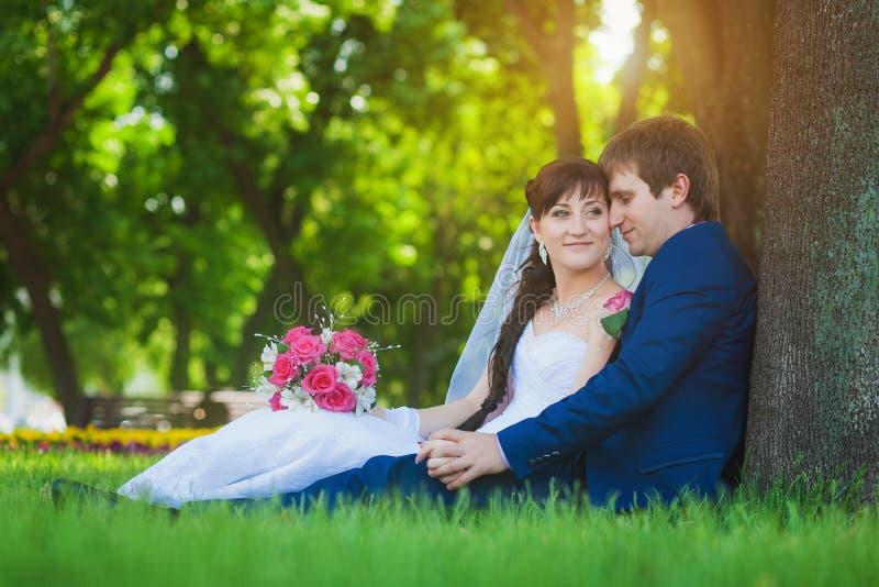 De gelukkige jonggehuwden zitten op het groene gras royalty-vrije stock afbeelding