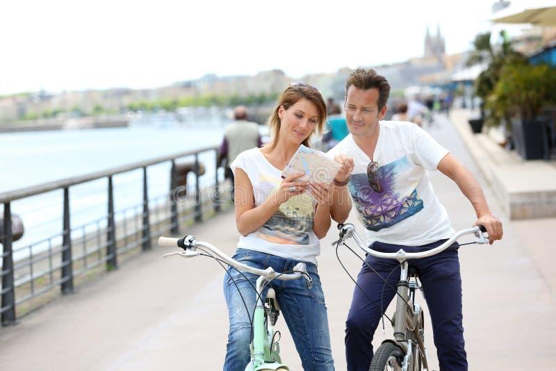 De gelukkige kaart van de paarlezing op fietsreis in stad royalty-vrije stock foto