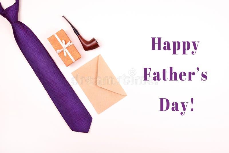 De gelukkige kaart van de Vaderdaggroet met samenstelling van halsband, giftdoos, ambachtenvelop en rokende pijp stock fotografie