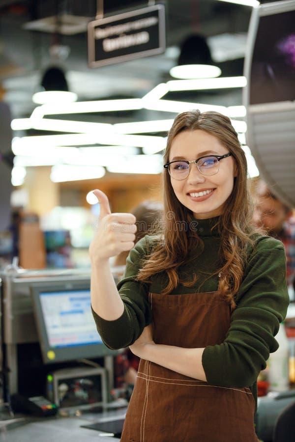 De gelukkige kassiersvrouw bij werkruimte het tonen beduimelt omhoog stock foto