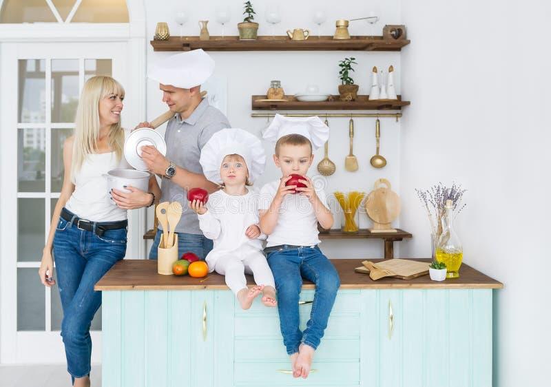 De gelukkige Kaukasische familie in witte kappen met twee jonge geitjes is in huiskeuken stock foto