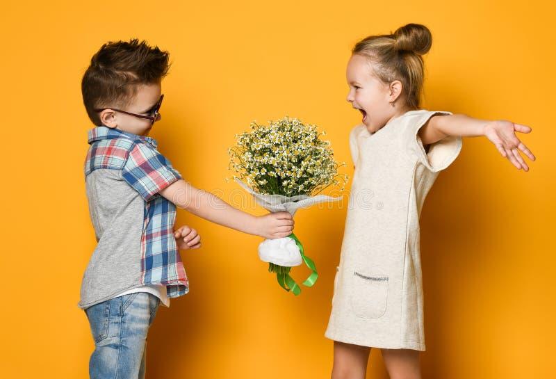 De gelukkige Kaukasische mensenjongen geeft bloemen aan zijn meisje dat over gele achtergrond wordt ge?soleerd royalty-vrije stock foto's