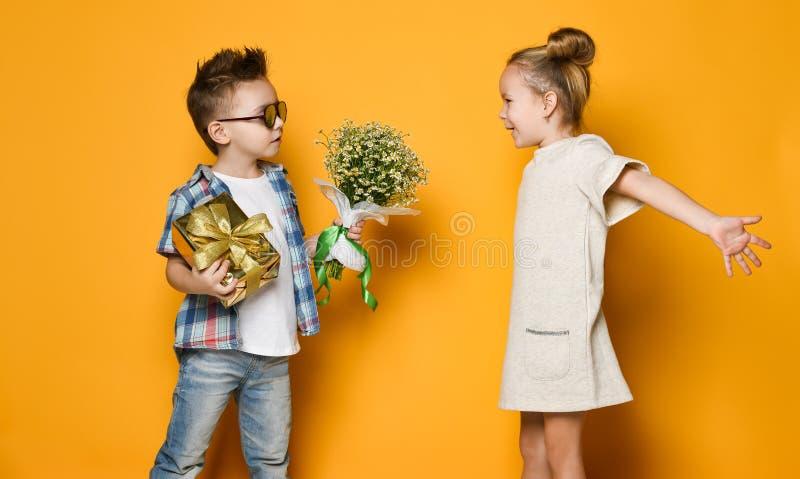 De gelukkige Kaukasische mensenjongen geeft bloemen aan zijn meisje dat over gele achtergrond wordt ge?soleerd stock foto