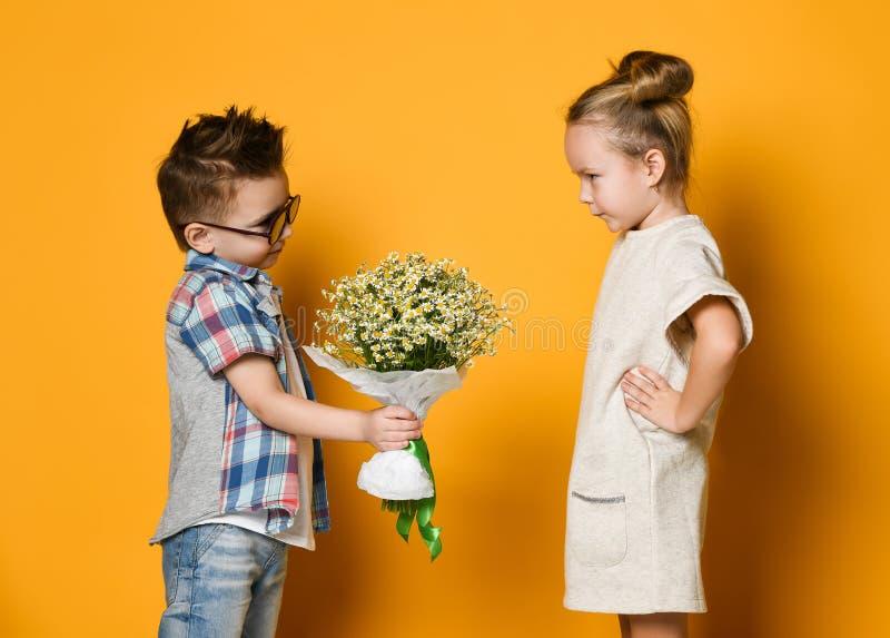 De gelukkige Kaukasische mensenjongen geeft bloemen aan zijn meisje dat over gele achtergrond wordt ge?soleerd royalty-vrije stock fotografie
