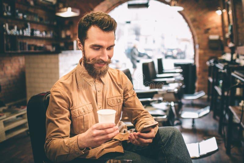 De gelukkige kerel bekijkt de telefoon en het glimlachen Hij houdt een kop thee in rechts en geniet van het ogenblik royalty-vrije stock fotografie