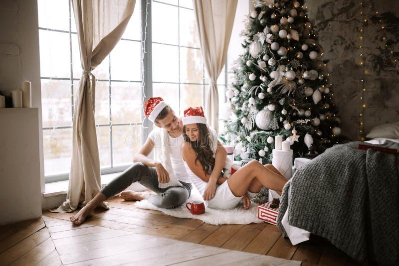 De gelukkige kerel en het meisje in witte t-shirts en Santa Claus-hoeden zitten en koesteren in de ruimte op de vloer voor royalty-vrije stock afbeelding