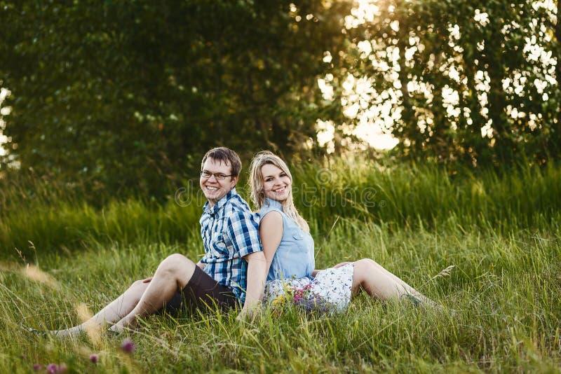 De gelukkige kerel en het meisje zitten op het gras in de zomer royalty-vrije stock afbeeldingen