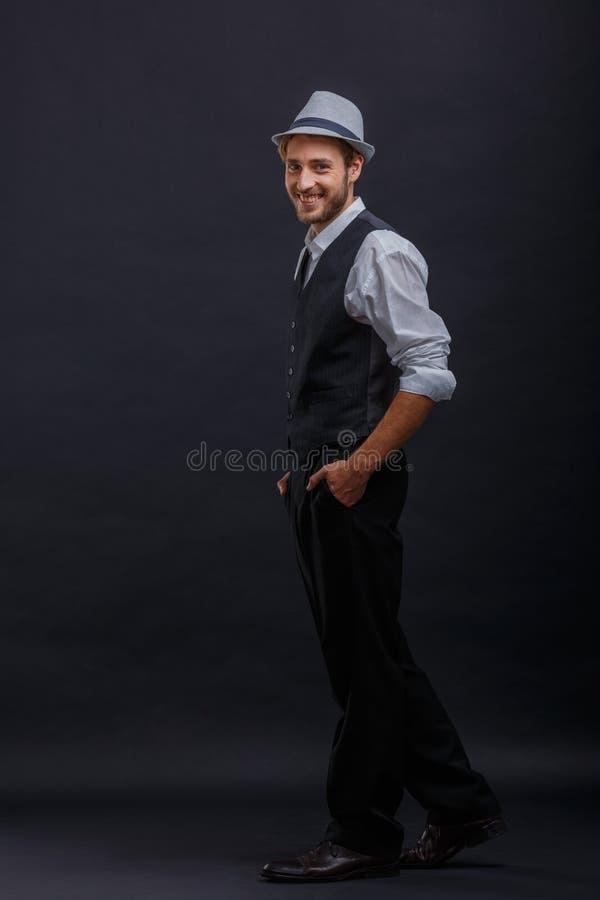 De gelukkige kerel in retro kostuum en hoed, die het houden dient zakken in zich zijdelings bevinden stock afbeelding