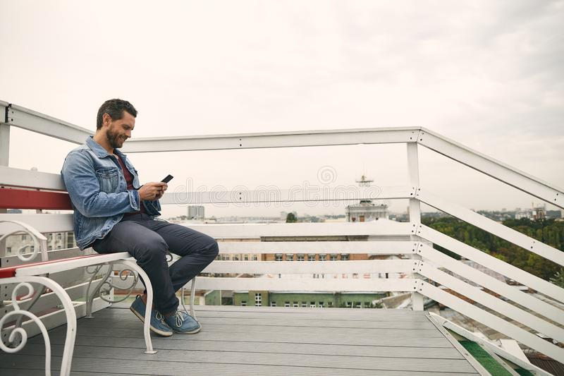 De gelukkige kerel zit in openlucht op leuk terras stock fotografie