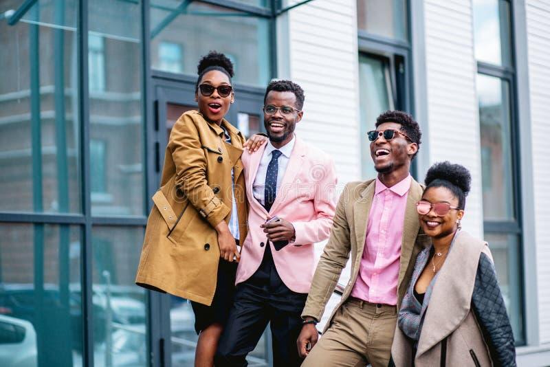 De gelukkige kerels met meisjes hebben pret op de straat royalty-vrije stock afbeeldingen