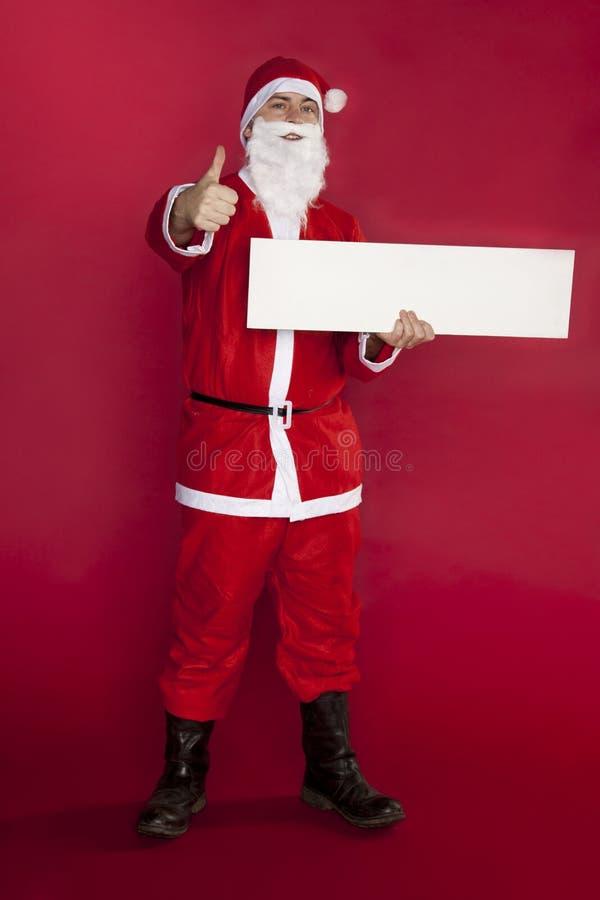 De gelukkige Kerstman houdt een plaats voor reclame, duim omhoog en c royalty-vrije stock foto's