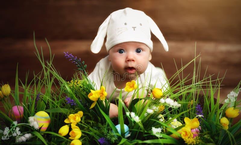 De gelukkige kindbaby kleedde zich als Paashaaskonijn op het gras stock afbeeldingen