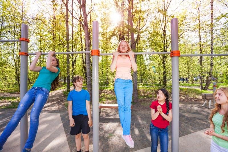 De gelukkige kinderen chinning omhoog op de speelplaats royalty-vrije stock afbeeldingen
