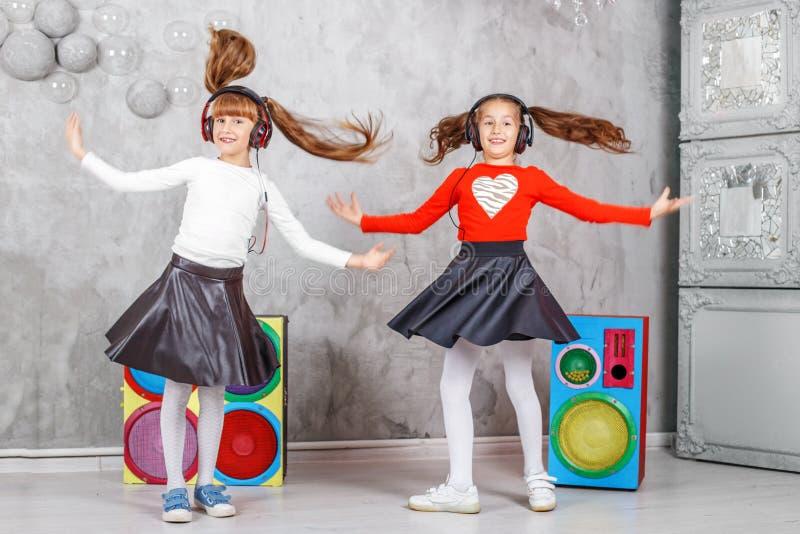 De gelukkige kinderen dansen en luisteren aan muziek in hoofdtelefoons Conc stock fotografie