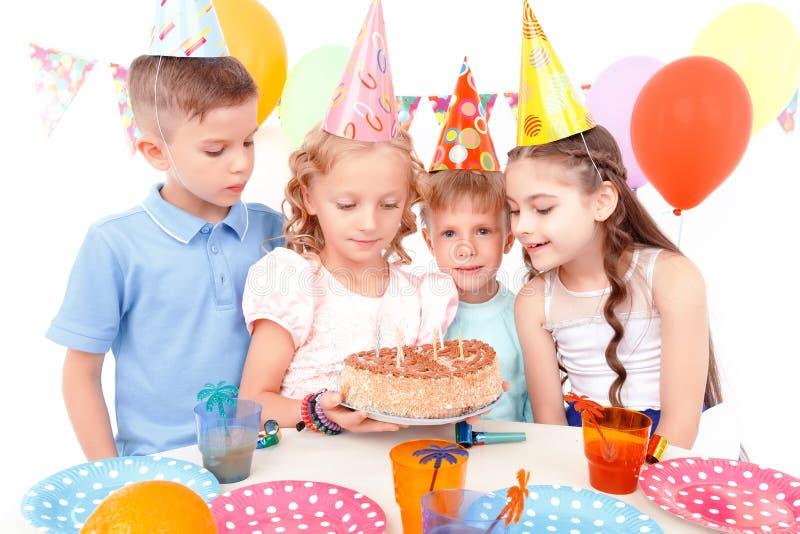 De gelukkige kinderen die met verjaardag stellen koeken royalty-vrije stock afbeeldingen