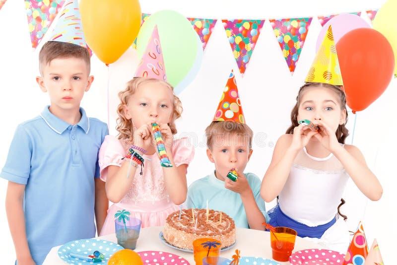 De gelukkige kinderen die met verjaardag stellen koeken royalty-vrije stock afbeelding